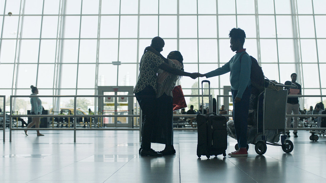 man hugging wife in airport and holding hands with daughter