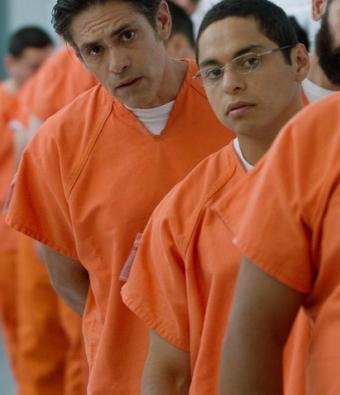 Men in a detention facility wearing orange uniforms